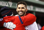 Boston Red Sox's J.D. Martinez gets a hug in the dugout after hitting a home run against the Colorado Rockies during the third inning of a baseball game Tuesday, May 14, 2019, at Fenway Park in Boston. (AP Photo/Winslow Townson)