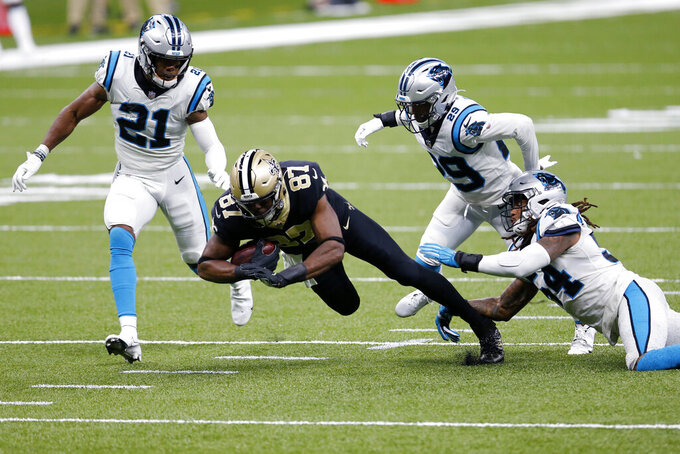 New Orleans Saints tight end Jared Cook (87) is brought down by Carolina Panthers outside linebacker Shaq Thompson (54), cornerback Corn Elder (29) and outside linebacker Jeremy Chinn (21) in the first half of an NFL football game in New Orleans, Sunday, Oct. 25, 2020. (AP Photo/Brett Duke)