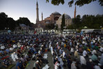 FILE - In this Friday, July 10, 2020, file photo, muslims offer their evening prayers outside the Byzantine-era Hagia Sophia, one of Istanbul's main tourist attractions in the historic Sultanahmet district of Istanbul, following Turkey's Council of State's decision that paved the way the landmark monument be turned from a museum into a mosque. Turkish President Recep Tayyip Erdogan is scheduled to join hundreds of worshipers Friday, July 24, for the first Muslim prayers at the Hagia Sophia in 86 years. (AP Photo/Emrah Gurel, File)