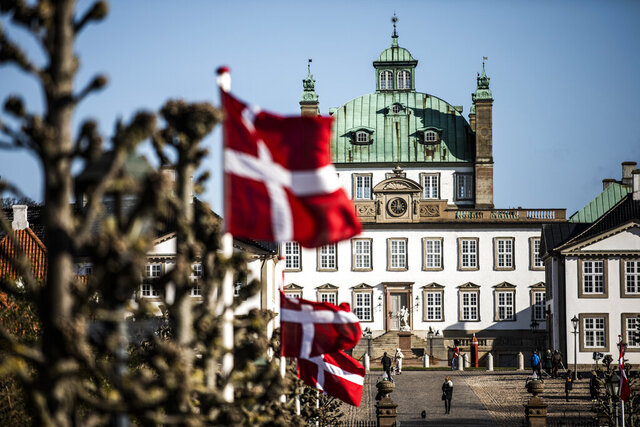 National flags are raised outside Fredensborg Castle, in Fredensborg, Denmark, Thursday, April 16, 2020. The Danish Queen Margrethe is celebrating her 80th birthday today but in private due to the new COVID-19 coronavirus pandemic. (Olafur Steinar Gestsson/Ritzau Scanpix via AP)