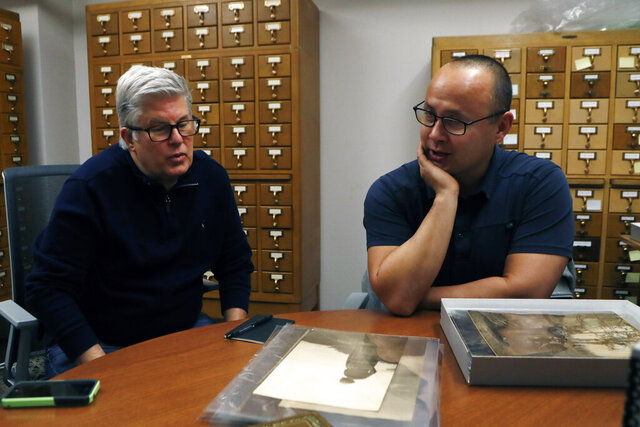 In this Thursday, Nov. 14, 2019 photo, Eric Hemenway, right, the director of archives and records for the Little Traverse Bay Band of Odawa Indians talks with collector Richard Pohrt Jr., at the University of Michigan William Clements Library in Ann Arbor, Mich. Hemenway was examining the photographs acquired by the library in 2016 from Pohrt Jr. which represent some 80 indigenous groups. (AP Photo/Carlos Osorio)