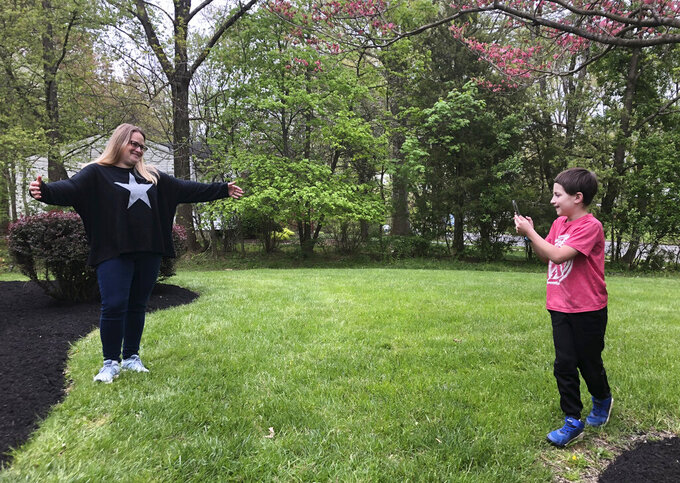 Jacob Cornfield, 8, takes a photo of his mother Abbye Cornfield on Wednesday, May 6, 2020 in Princeton, N.J. for his Mother's Day present. Mother's Day approaches and many dads are on their own this year to work with kids on hand-made gifts. (AP Photo/Josh Cornfield)