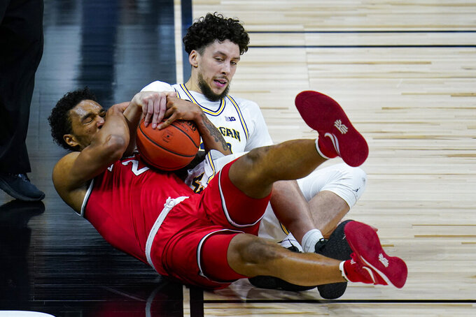 Michigan forward Brandon Johns Jr. (23) and Ohio State guard Musa Jallow (2) fight for a loose ball in the first half of an NCAA college basketball game at the Big Ten Conference tournament in Indianapolis, Saturday, March 13, 2021. (AP Photo/Michael Conroy)