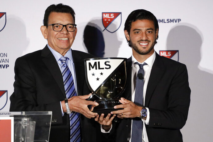 Former Los Angeles Dodgers pitcher Fernando Valenzuela, left, poses with Major League Soccer's Los Angeles FC player Carlos Vela and the Most Valuable Player trophy after Vela was presented with the award Monday, Nov. 4, 2019, in Los Angeles. Vela became the first Mexican player to win the MLS award. (AP Photo/Chris Carlson)