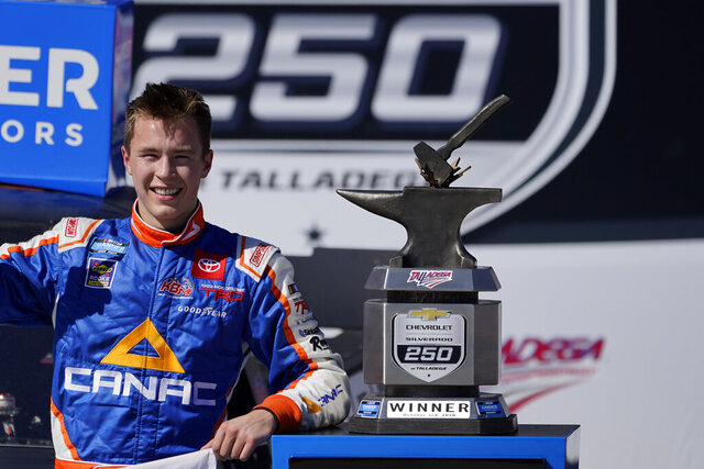 Raphael Lessard celebrates in Victory Lane after winning the NASCAR Truck series auto race at Talladega Superspeedway, Saturday, Oct. 3, 2020, in Talladega, Ala. (AP Photo/John Bazemore)