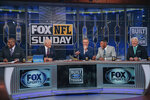 "In this 2018 photo provided by Fox Sports, Curt Menefee, Terry Bradshaw, Howie Long, Michael Strahan and Jimmy Johnson, from left, get ready for the ""Fox NFL Sunday"" pregame show during the 2018 season at the Fox Sports studio in Los Angeles. The show, which started in 1994, was inducted into the NAB Broadcasting Hall of Fame earlier this year. (Fox Sports via AP)"