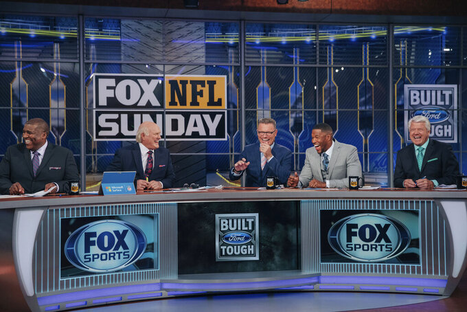 """In this 2018 photo provided by Fox Sports, Curt Menefee, Terry Bradshaw, Howie Long, Michael Strahan and Jimmy Johnson, from left, get ready for the """"Fox NFL Sunday"""" pregame show during the 2018 season at the Fox Sports studio in Los Angeles. The show, which started in 1994, was inducted into the NAB Broadcasting Hall of Fame earlier this year. (Fox Sports via AP)"""