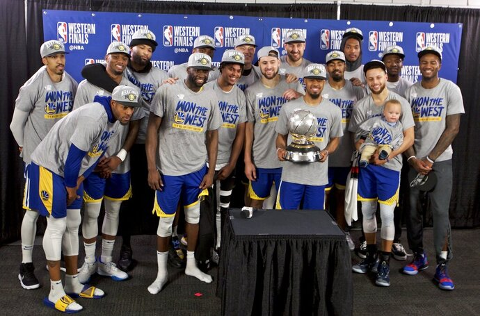 The Golden State Warriors players pose with the Western Conference Championship trophy after Game 4 of the NBA basketball playoffs Western Conference finals against the Portland Trail Blazers Monday, May 20, 2019, in Portland, Ore. The Warriors won 119-117 in overtime. (AP Photo/Craig Mitchelldyer)