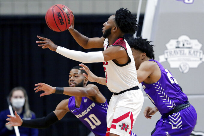 Nicholls State forward Najee Garvin, middle, passes the ball under pressure from Abilene Christian guards Reggie Miller (10) and Coryon Mason, right, during the first half of an NCAA college basketball game for the Southland Conference men's tournament championship Saturday, March 13, 2021, in Katy, Texas. (AP Photo/Michael Wyke)