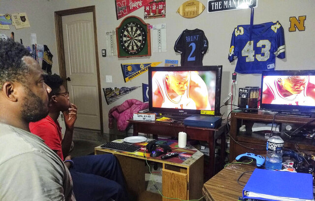 In this Sunday May 17, 2020, photo provided by Christina Mushi-Brunt, AP Sports Writer Cliff Brunt and his 14-year-old son, Elias, watch the final episodes of The Last Dance in Oklahoma City. For the past five weeks, the docuseries that revisited Michael Jordan's basketball career gave them something to look forward to during the coronavirus pandemic and helped them connect their generations. (Christina Mushi-Brunt via AP)