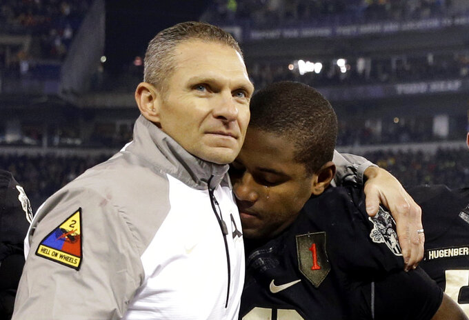 FILE - In this Dec. 13, 2014, file photo, Army head coach Jeff Monken, left, embraces running back Larry Dixon after losing 17-10 to Navy, in Baltimore. With Army ranked No. 22, the Cadets (9-2) try to beat Navy (3-9) for the third straight time Saturday in the storied series.(AP Photo/Patrick Semansky, File)