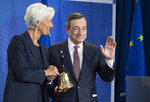 Outgoing European Central Bank President Mario Draghi waves next to his designated successor Christine Lagarde, at a ceremony celebrating the change at the head of the ECB in Frankfurt, Germany, Monday, Oct. 28, 2019. Draghi leaves as head of the European Central Bank credited with having rescued the eurozone from disaster with a well-timed phrase and bold action to back up his words. (Boris Roessler/Pool Photo via AP)
