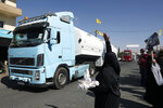 A Hezbollah supporter throws rice over a convoy of tanker trucks carrying Iranian diesel crossed the border from Syria into Lebanon, arrive at the eastern town of el-Ain, Lebanon, Thursday, Sept. 16, 2021. The delivery violates U.S. sanctions imposed on Tehran after former President Donald Trump pulled America out of a nuclear deal between Iran and world powers three years ago. (AP Photo/Bilal Hussein)