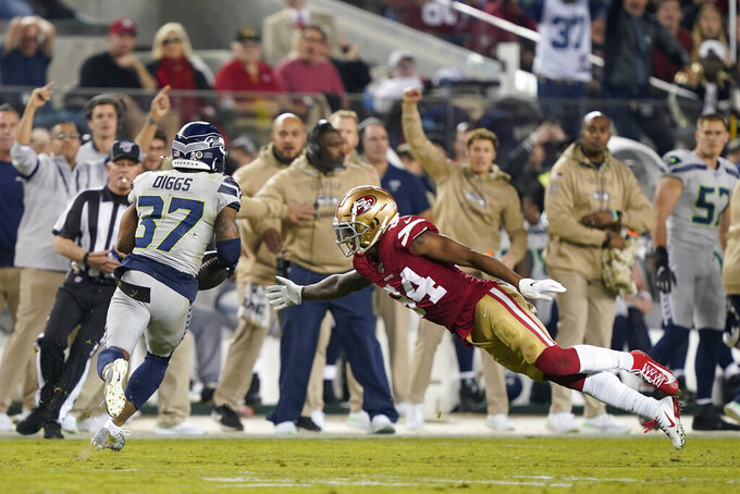 Seattle Seahawks defensive back Quandre Diggs (37) runs after intercepting a pass against San Francisco 49ers wide receiver Kendrick Bourne (84) during the second half of an NFL football game in Santa Clara, Calif., Monday, Nov. 11, 2019. (AP Photo/Tony Avelar)