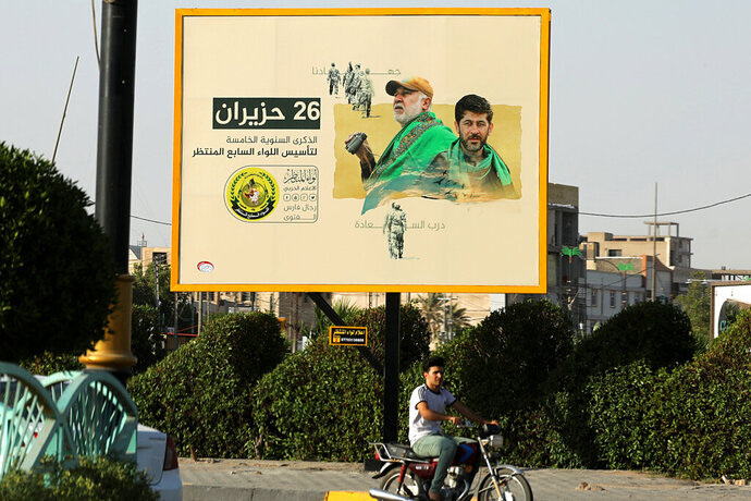 In this Tuesday, July 2, 2019 photo, motorists pass by a Popular Mobilization poster of volunteer militants who were killed in Iraq fighting Islamic State militants in Basra, Iraq. The Iraqi government's move to place Iranian-backed militias under the command of the armed forces is a political gamble by a prime minister increasingly caught in the middle of a dangerous rivalry between Iran and the U.S., the two main power brokers in Iraq.  (AP Photo/Nabil al-Jurani)