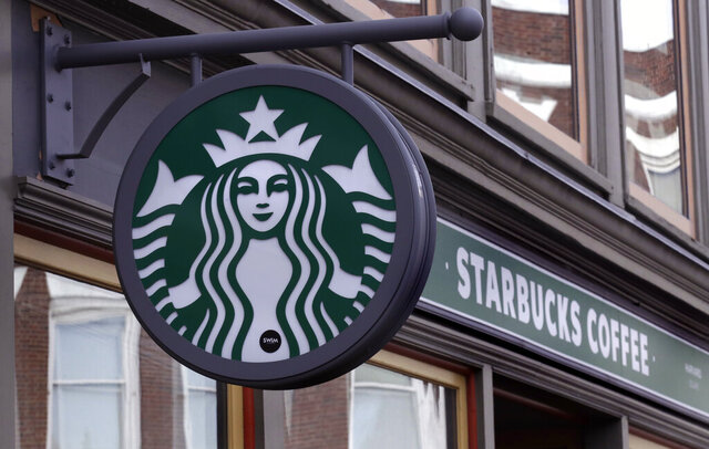 FILE- This Dec. 13, 2018, file photo shows a sign for a Starbucks Coffee shop in Harvard Square in Cambridge, Mass. Starbucks says it's seeing steady recovery as its stores reopen, but it expects the impact of the new coronavirus to last well into the fall. The coffee giant said Tuesday, July 28, 2020 that revenue in its fiscal third quarter plummeted 38% to $4.2 billion. (AP Photo/Charles Krupa, File)