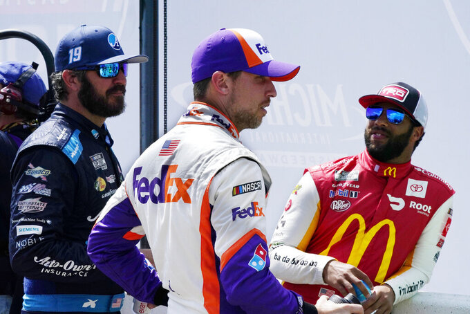 Denny Hamlin, center, talks with Martin Truex Jr., left, and Bubba Wallace before driver introductions at the NASCAR Cup Series auto race at Michigan International Speedway, Sunday, Aug. 22, 2021, in Brooklyn, Mich. (AP Photo/Carlos Osorio)