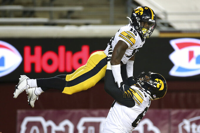 Iowa offensive lineman Justin Britt (63) lifts running back Tyler Goodson (15) in celebration after Goodson scored a touchdown against Minnesota during the first half of an NCAA college football game Friday, Nov. 13, 2020, in Minneapolis. (AP Photo/Stacy Bengs)