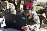 In this Friday, May 15, 2020 photo, a Fort Bragg, North Carolina paratrooper checks off deploying soldiers' names on a computer. 2,200 members of the 82nd Airborne's 2nd Brigade Combat Team will be deploying to the Middle East for nine months amid the Coronavirus pandemic. (AP Photo/Sarah Blake Morgan)
