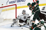 Minnesota Wild's Nick Bjugstad, right, attempts to make a shot as Los Angeles Kings' goalie Calvin Petersen stops the attempt in the first period of an NHL hockey game, Tuesday, Jan. 26, 2021, in St. Paul, Minn. (AP Photo/Jim Mone)