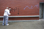 A worker removes graffiti from a Bank of America branch, Wednesday, Oct. 28, 2020, on Court Street in the Boerum Hill neighborhood of the Brooklyn borough of New York. Demonstrators protesting the police shooting of a Black man in Philadelphia broke store windows, set fires and vandalized police cars in Brooklyn Tuesday night, police said. (AP Photo/Mary Altaffer)
