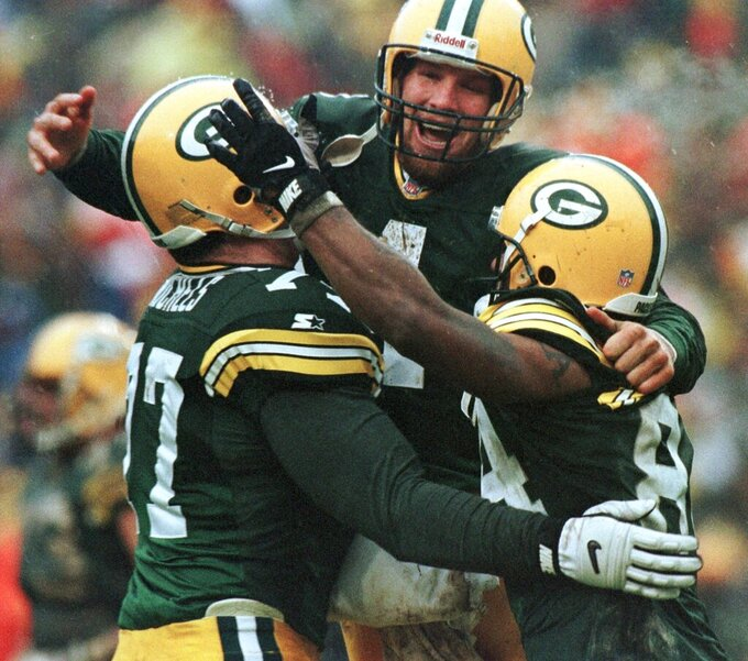 FILE - This Jan. 4, 1997, file photo shows Green Bay Packers, from left, John Michels, Brett Favre and Andre Rison celebrating after Green Bay's Antonio Freeman recovered a fumble by teammate Edgar Bennett for a touchdown in the third quarter against the San Francisco 49ers in Green Bay, Wisc. The Packers and 49ers that have combined for nine Super Bowl titles will meet with a spot in the ultimate game on the line once again when the 49ers (14-3) host the Packers (14-3) in the NFC championship game on Sunday, Jan. 19, 2020.(AP Photo/Morry Gash, file)