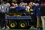 Michigan running back Berkley Edwards (32) is carted off the field past the Indiana bench during the second half of an NCAA college football game in Ann Arbor, Mich., Saturday, Nov. 17, 2018. Indiana linebacker Cam Jones was penalized and ejected for targeting on the play. (AP Photo/Paul Sancya)
