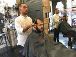 Rado Asatrian cuts a customer's hair at Man-oj hair salon in London's financial district, Thursday, Sept. 9, 2021. Before COVID-19, Asatrian usually had 10 to 15 customers a day, but now it's down to three or four. (AP Photo/Kelvin Chan)