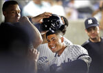 New York Yankees' Gleyber Torres celebrates with teammates in the dugout after hitting a solo home run during the fourth inning of the team's baseball game against the Texas Rangers, Wednesday, Sept. 4, 2019, in New York. Aaron Judge removes Torres's helmet. (AP Photo/Kathy Willens)