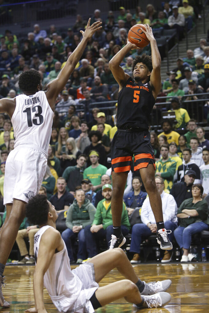 Oregon State's Ethan Thompson, right, shoots over Oregon's Chandler Lawson, left, and Will Richardson, bottom, during the second half of an NCAA college basketball game in Eugene, Ore., Thursday, Feb. 27, 2020. (AP Photo/Chris Pietsch)