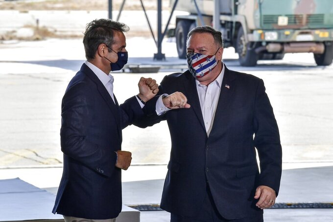 US Secretary of State Mike Pompeo, right, and Greek Prime Minister Kyriakos Mitsotakis pose during their visit at the Naval Support Activity base at Souda, on the Greek island of Crete, Tuesday, Sept. 29, 2020. Pompeo visited a U.S. naval base at Souda Bay on the southern Greek island of Crete Tuesday, ahead of a meeting with Greece's prime minister on the second day of his trip to the country. (Aris Messinis/Pool viaAP)