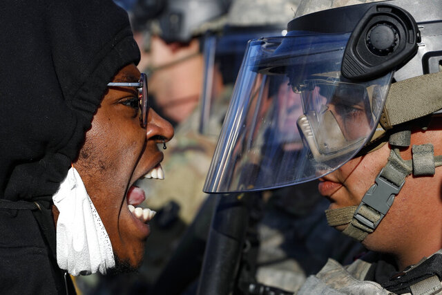 Protesters and National Guardsmen face off on East Lake Street, Friday, May 29, 2020, in St. Paul, Minn.  The massive protests sweeping across U.S. cities following the police killing of a black man in Minnesota have elevated fears of a new surge in cases of the coronavirus. Images showing thousands of screaming, unmasked protesters have sent shudders through the health community, who worry their calls for social distancing during the demonstrations are unlikely to be heard.   (AP Photo/John Minchillo)