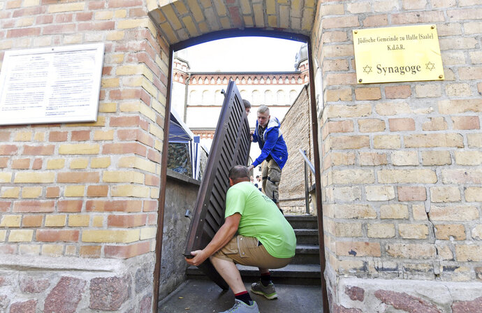 Carpenter Thomas Thiele, front, removes the bullet hole-ridden door of synagogue in Halle, Germany, Monday, July 28, 2020. The door is slated to become part of a memorial and a new one is being installed in its place. On Oct. 9, 2019 a man repeatedly tried, but failed, to force his way into the synagogue with 52 worshippers inside, before shooting and killing a woman in the street outside and a man at a nearby kebab shop. (Hendrik Schmidtpa/dpa via AP)