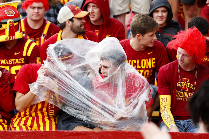 Iowa State fans take cover during a lightning delay in the first half of an NCAA college football game against Iowa, Saturday, Sept. 14, 2019, in Ames, Iowa. (AP Photo/Charlie Neibergall)