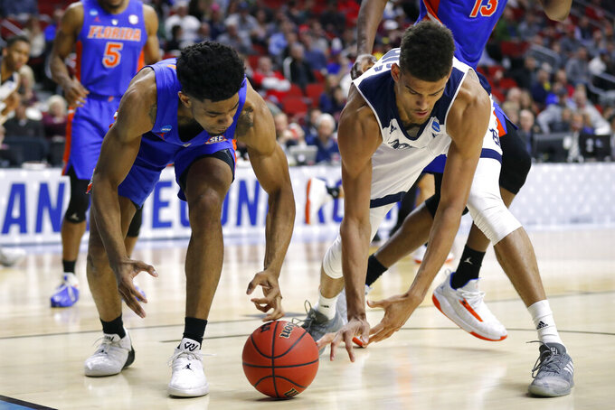 Florida guard Jalen Hudson, left, fights for a loose ball with Nevada forward Trey Porter during a first round men's college basketball game in the NCAA Tournament, Thursday, March 21, 2019, in Des Moines, Iowa. (AP Photo/Charlie Neibergall)