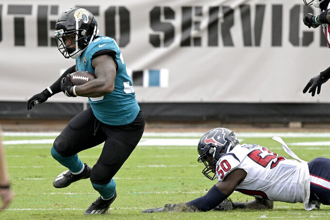 Jacksonville Jaguars running back James Robinson, left, runs past Houston Texans linebacker Tyrell Adams (50) during the second half of an NFL football game, Sunday, Nov. 8, 2020, in Jacksonville, Fla. (AP Photo/Phelan M. Ebenhack)