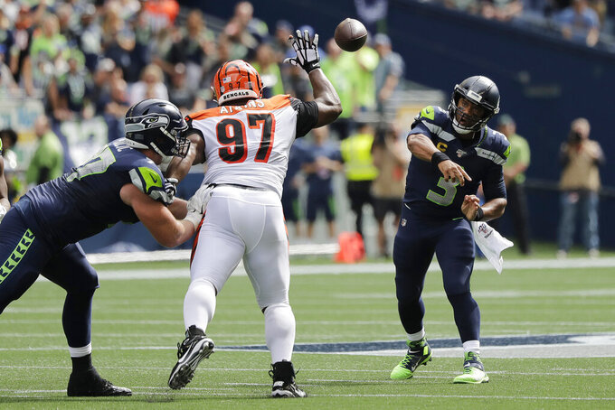 Seattle Seahawks quarterback Russell Wilson, right, passes under pressure from Cincinnati Bengals defensive tackle Geno Atkins (97) during the first half of an NFL football game, Sunday, Sept. 8, 2019, in Seattle. (AP Photo/John Froschauer)