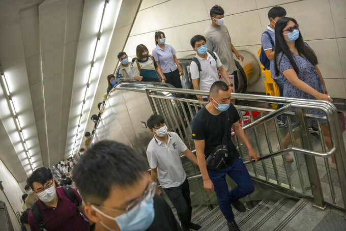 People wearing face masks to protect against COVID-19 walk up stairs in a subway station during the morning rush hour in Beijing, Wednesday, Aug. 4, 2021. The coronavirus's delta variant is challenging China's costly strategy of isolating cities, prompting warnings that Chinese leaders who were confident they could keep the virus out of the country need a less disruptive approach. (AP Photo/Mark Schiefelbein)