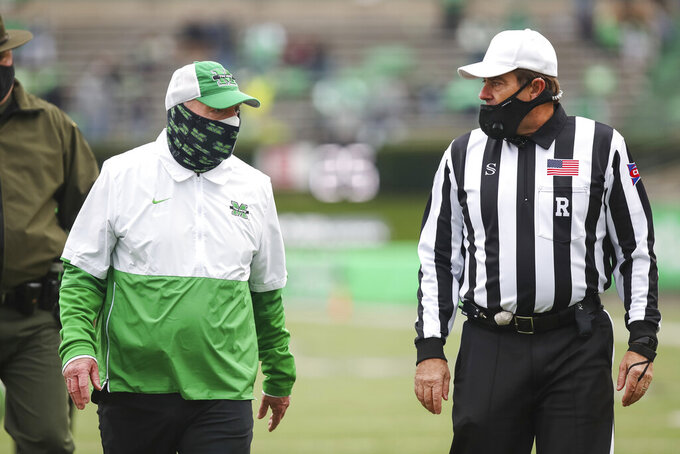 Marshall head coach Doc Holliday talks with an official as the exits the field at halftime of an NCAA college football game on Saturday, Dec. 5, 2020, in Huntington, W.Va.  (Sholten Singer/The Herald-Dispatch via AP)