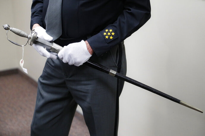 A sword, wielded in the American Revolution and the War of 1812, is handled by Hamilton County Sheriff Jim Neil during a news conference to update the investigation into its ownership, Wednesday, Nov. 6, 2019, in Cincinnati. Police in Connecticut seized the sword, believed to have been stolen in Cincinnati some 40 years ago, last month just hours before it was going up for auction. (AP Photo/John Minchillo)