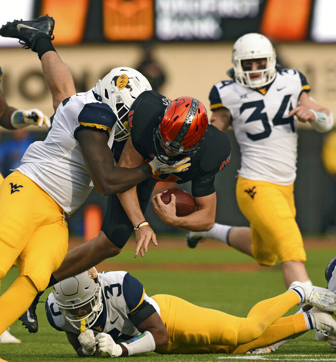 West Virginia linebacker Shea Campbell, right, watches as Oklahoma State quarterback Taylor Cornelius, center, jumps over West Virginia safety Toyous Avery Jr, down, while being tackled by defensive lineman Dante Stills during the first half of an NCAA college football game in Stillwater, Okla., Saturday, Nov. 17, 2018. Cornelius had 106 yards rushing in the 45-41 Oklahoma State upset over West Virginia.(AP Photo/Brody Schmidt)