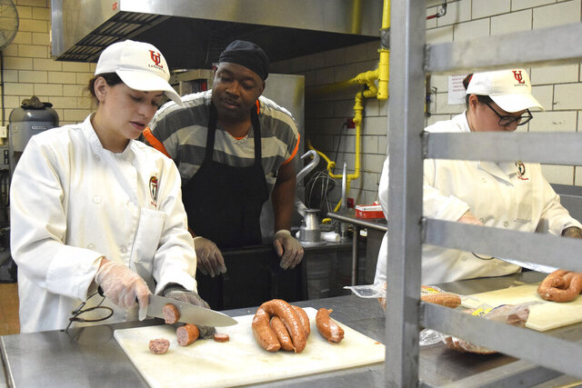 In this Feb. 11, 2020 photo, University of Louisiana-Lafayette students Kelu Archbold, left, and Kaylin Miller, right, listen as Chad Williams, a head chef inmate at the Lafayette Parish Correctional Center in Lafayette, La., gives directions in the jail's kitchen on. Archbold and Miller are both seniors in the hospital management program and are completing their internship at the correctional center. (Ashley White/The Daily Advertiser via AP)