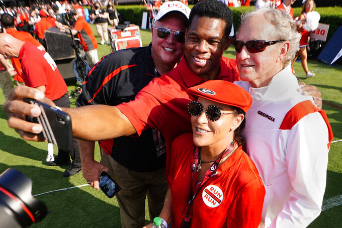 Former Georgia running back and Republican candidate for U.S. Senate, Herschel Walker, center, takes a photo of himself, Kevin Jackson, left, Mike Kaven, right, and his wife, Julie, during halftime of a an NCAA college football game between Georgia and UAB, Saturday, Sept. 11, 2021, in Athens, Ga. (AP Photo/John Bazemore)