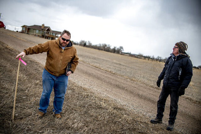 In this Tuesday, Feb. 25, 2020 photo, Ted Simmons, left, shows the survey stakes marking the location of the proposed easement across his property during a meeting with a Tribune reporter and other affected property owners at Ken and Sue Jesse Kerchenfaut's home in unincorporated Weld County, Colo. near the Larimer county line. The city of Thornton is seeking a permanent easement across the Kerchenfaut's and Simmons's properties, among others, to build a pipeline to carry water from an irrigation ditch branching off the Cache la Poudre River to Thornton. (Alex McIntyre/The Greeley Tribune via AP)