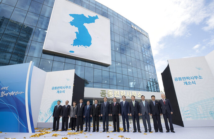 South Korea's Unification Minister Cho Myoung-gyon, seventh from left, and Ri Son Gwon, chairman of the North's Committee for the Peaceful Reunification, sixth from right, pose for photograph with other participants during an opening ceremony for two Koreas' first liaison office in Kaesong, North Korea, Friday Sept. 14, 2018. The rival Koreas on Friday launched their first liaison office near their tense border to facilitate better communication and exchanges ahead of their leaders' summit in Pyongyang next week. (Korea Pool/Yonhap via AP)