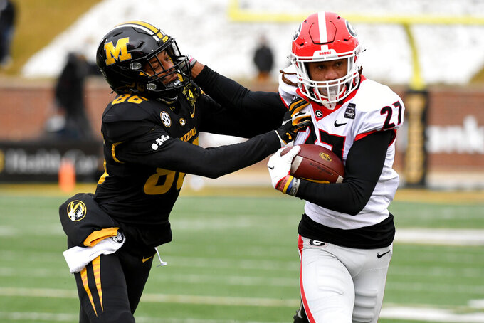 Georgia defensive back Eric Stokes (27) runs with the ball after intercepting a pass as Missouri wide receiver Tauskie Dove (86) defends during the first half of an NCAA college football game Saturday, Dec. 12, 2020, in Columbia, Mo. (AP Photo/L.G. Patterson)