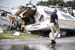 Bill Bailey, assistant chief of the Emerald Isle Police Department, walks past a damaged trailer in the Holiday Trav-l Park on Thursday, Sept. 5, 2019, in Emerald Isle, N.C, after a possible tornado generated by Hurricane Dorian struck the area. (Julia Wall/The News & Observer via AP)