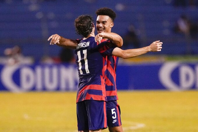 United States' Antonee Robinson, right, and his teammate Brenden Aaronson celebrate at the end of the game against Honduras during a qualifying soccer match for the FIFA World Cup Qatar 2022, in San Pedro Sula, Honduras, Wednesday, Sept. 8, 2021. United States won 4-1. (AP Photo/Moises Castillo)