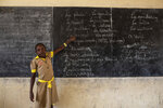 In this photo provided by UNICEF and taken on May 26, 2019, A student goes over blackboard notes for a class in emergency preparedness at a school in Baigai, Cameroon. More than 9,000 schools have closed and more than 1.9 million children in West and Central Africa have been forced out of school because of increasing violence in the region and attacks specifically targeting education facilities, UNICEF said Friday, Aug, 23. Attacks on schools in Mali, Burkina Faso and Niger, where an Islamic extremist insurgency has grown, have doubled in the past two years, the agency said. (Tanya Bindra/UNICEF via AP)