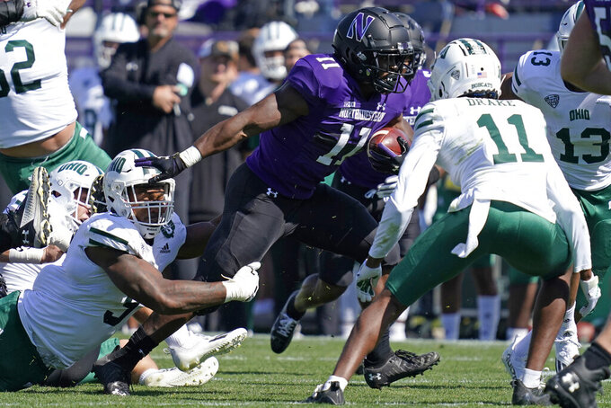 Northwestern running back Andrew Clair, center, (11) runs with the ball against Ohio defensive end Will Evans, left, and safety Tariq Drake (11) during the first half of an NCAA college football game in Evanston, Ill., Saturday, Sept. 25, 2021. (AP Photo/Nam Y. Huh)